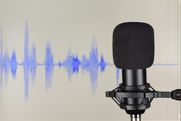 Black studio condenser microphone over computer monitor background with waveform. sound recording concept