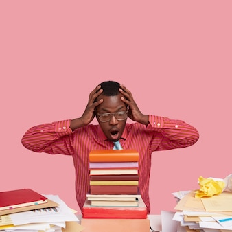 Black stupefied young teacher keeps hands on head, opens mouth widely, stares at pile of books, prepares lecture for students