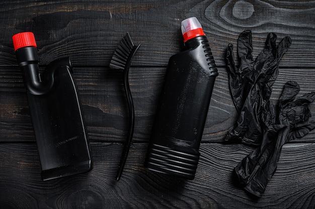 消耗品を備えたブラックスタイルのホームクリーニングサービスのコンセプト。黒の木製の背景。上面図。