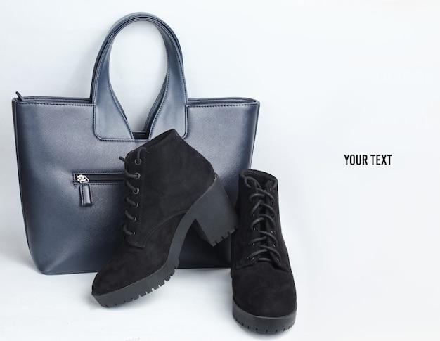 블랙 스웨이드 부츠와 흰색 배경에 가죽 패션 가방. 공간 복사