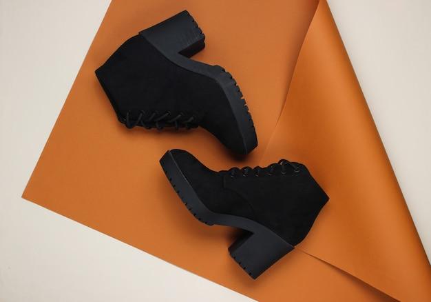 Черные замшевые сапоги на сложенной бумаге