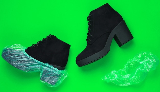 Black suede boots with shoe covers on green background. top  view