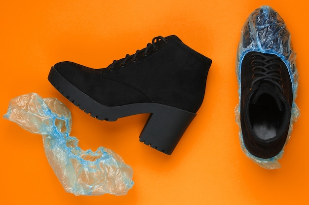 Black suede boots with shoe covers on orange background. top  view