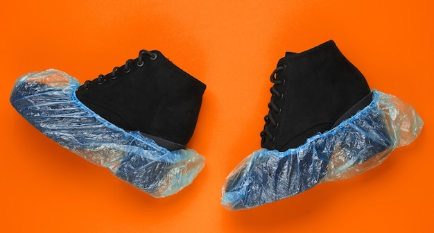 Black suede boots with shoe covers on orange background. over view