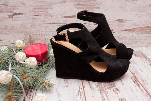 Black suede shoes on a wooden background, fir branch, garland and candle