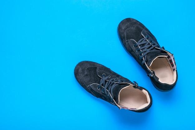 青い背景の黒いスエードスポーツシューズ。上からの眺め。おしゃれな発想。フラット横たわっていた。