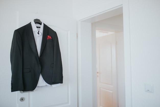 黒のスーツとシャツがハンガーからドアにぶら下がっています。