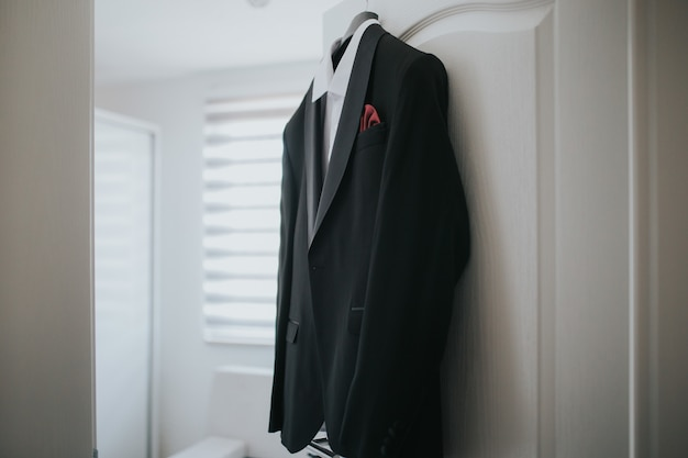 Black suit and a white shirt is hanging from hanger from the door