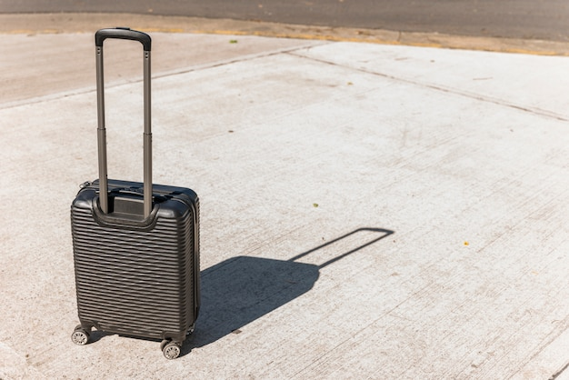 Black suitcase for travelling on the street