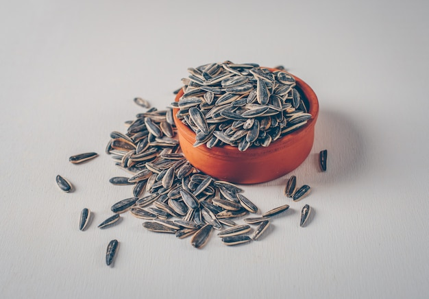 Black sunflower seeds in a bowl on a white background. high angle view.