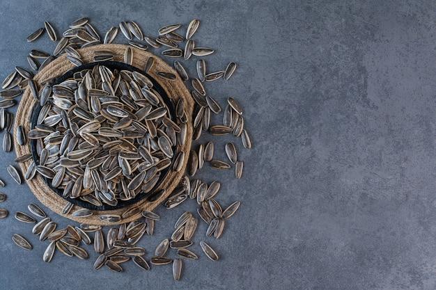 Черные семена подсолнечника в миске на подставке на мраморной поверхности