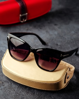 Black sunglasses around cream and red cases on the grey surface