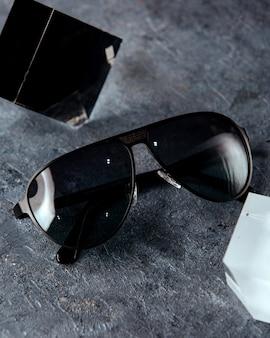 Occhiali da sole neri sulla superficie grigia