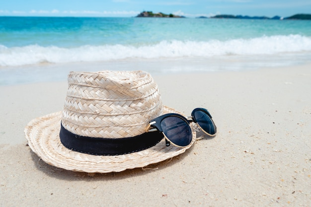 Black sunglasses and hat on the sea