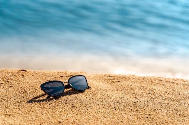黄色の砂と海または海に黒のサングラス。テキストまたは製品用のスペース。夏休み