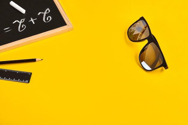Черные солнцезащитные очки, карандаш, линейка и пример два плюс два, написанные мелом