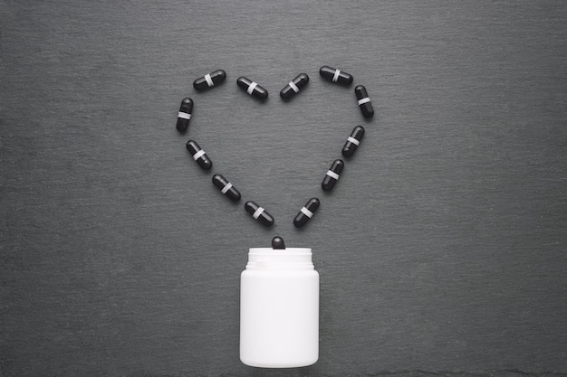 Black supplement capsules arranged in heart shape are poured from white bottle. top view, flat lay, copy space. medicine theme, health care concept.