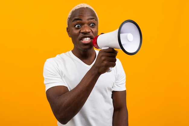 Черный удивленный американский мужчина в белой футболке рассказывает новости через мегафон на изолированном апельсине