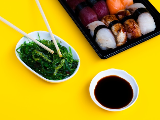 Black sushi plate with seaweed salad and soy sauce on a yellow background