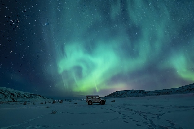 Suv nero sul campo innevato sotto le luci verdi dell'aurora