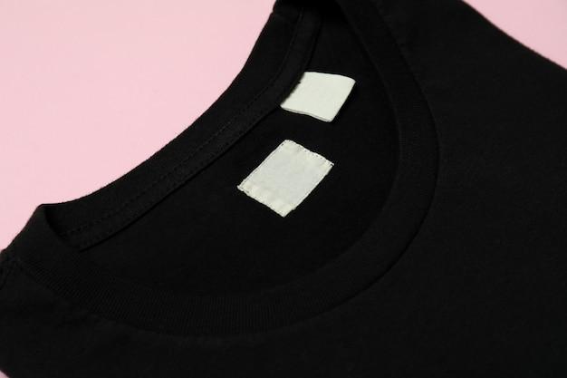 ピンクの背景に黒のスウェットシャツ
