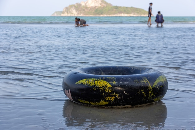 A black swim ring on a sandy ocean beach