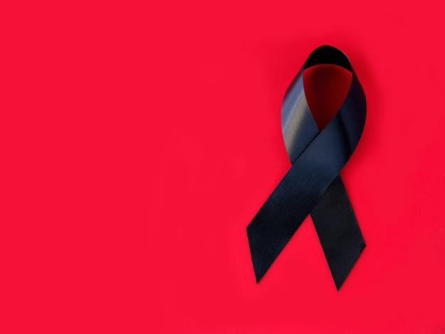 Черная символическая лента на красной поверхности