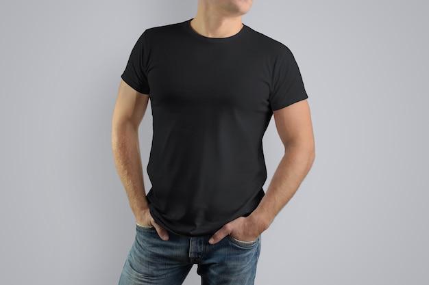 灰色の壁に分離されたブルージーンズの強い男に黒のtシャツ。
