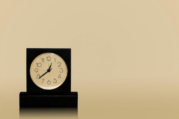 Черные настольные часы с белым циферблатом, стоящие на темном столе, изолированные на темном фоне