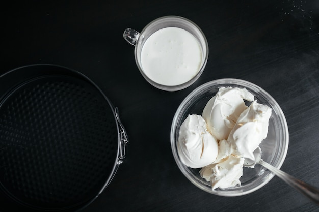 On a black table is a baking dish, cream and curd cheese in a cup
