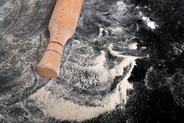 小麦粉をまぶした黒いテーブル、生地用めん棒
