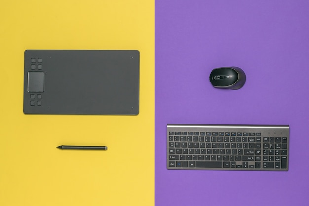 노란색과 보라색에 검은 태블릿 및 키보드. 컴퓨터 용 주변 장치.