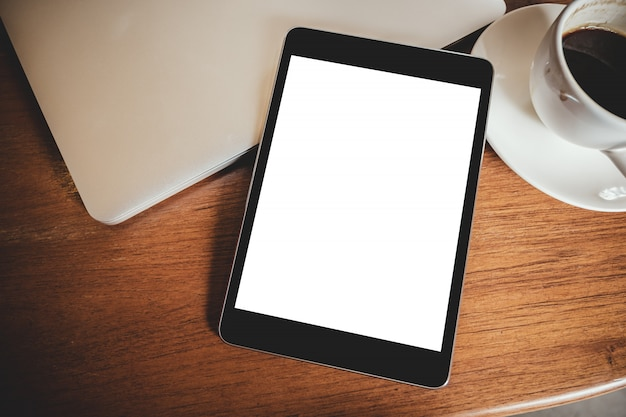 木製のテーブルにノートパソコンとコーヒーカップと空白のデスクトップの白い画面と黒いタブレットpc