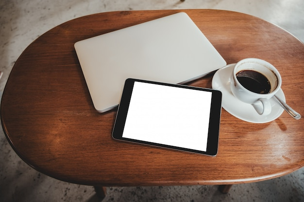 Black tablet pc with blank desktop white screen with laptop and coffee cup on wooden table