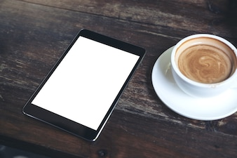 Black tablet with white blank desktop screen and coffee cup on vintage wooden table