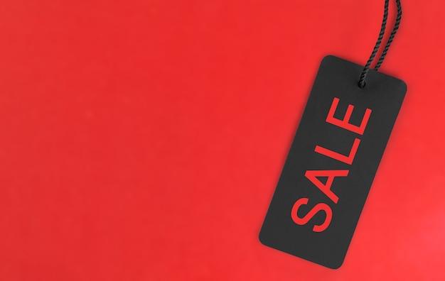 碑文セールと赤い背景の上の黒いタグ