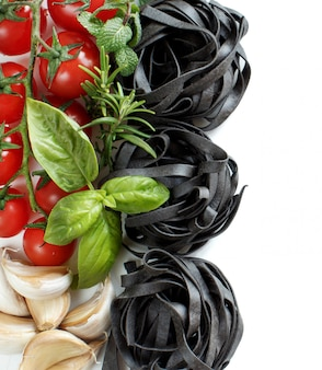 チェリートマト、ニンニク、ハーブを白で隔離される黒タリアテッレパスタをクローズアップ