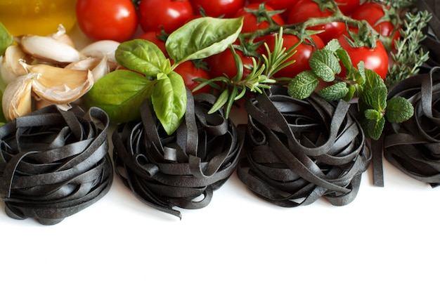 Black tagliatelle pasta with cherry tomatoes, garlic and herbs isolated on white, close up