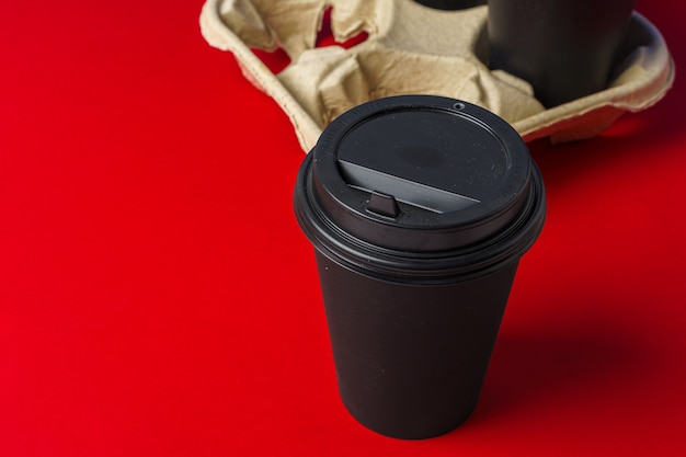 Black take away coffee cups in holder on table