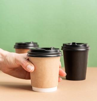 Черные бумажные кофейные чашки на вынос на зеленом и коричневом фоне