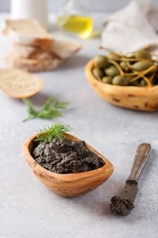블랙 타페나드 또는 타파스, 전통적인 프로방스 요리 또는 오래된 나무 테이블 배경에 올리브와 바질을 곁들인 딥. 선택적 초점입니다. 평면도