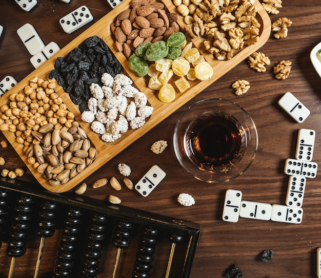 Black tea in armudu glass with various sweets and dominoes on the table