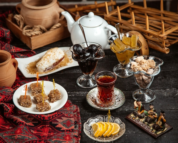 Black tea in armudu glass with various sweets