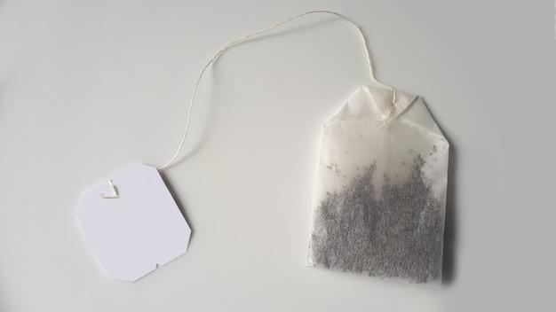 灰色の白い背景に白いラベルが付いた黒いティーバッグ白いティーバッグ