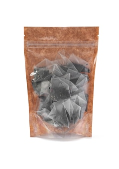 Black tea bags in a brown paper bag. doy-pack with a plastic window for bulk products. close-up. white background. isolated.