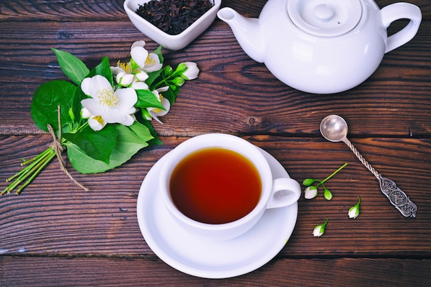 Black tea and a bouquet of blossoming jasmine