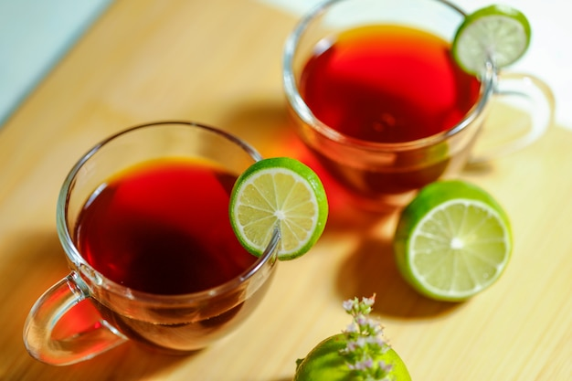 Black tea in cup with lemon