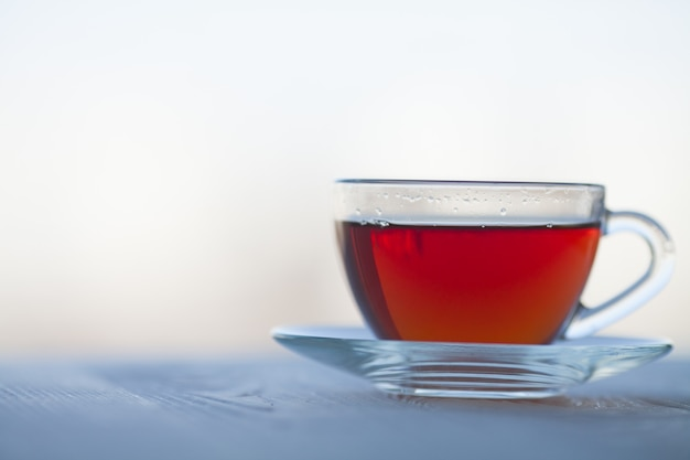 Black tea in glass cup on blurred background.