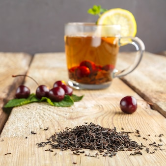 Black tea in a glass cup with mint cherries and lemon on a wooden table next to fresh cherries and sprinkled tea leaves. horizontal photo