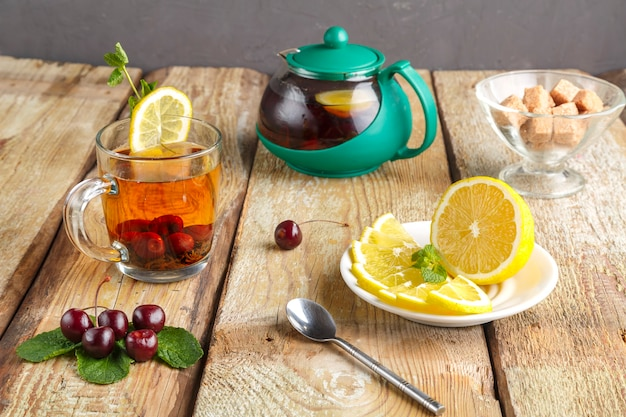 Black tea in a glass cup with mint cherries and lemon on a wooden table next to fresh cherries and a teapot and lemon in a plate.